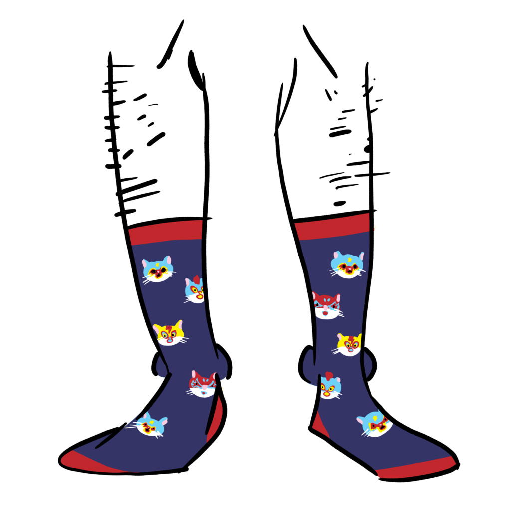 Blue socks with the faces of cats as a pattern. The cats are wearing luchadore masks.